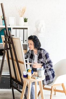 Artiste femme créative peignant une image travaillant dans son studio