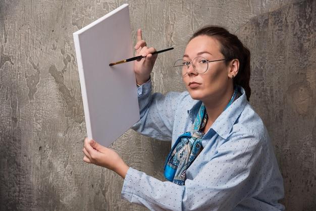 L'artiste de femme montre sa toile avec le pinceau sur le marbre