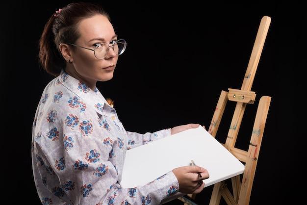 L'artiste de femme montre sa toile avec le pinceau sur le noir