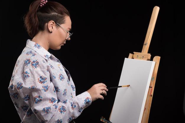 L'artiste de femme peint une image sur la toile avec le crayon sur le noir