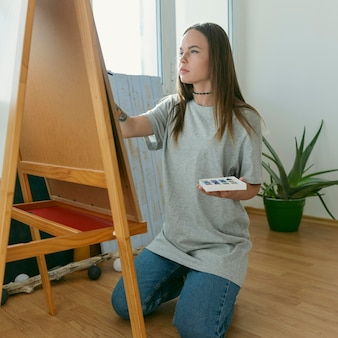 Artiste femme peinture sur toile vue latérale