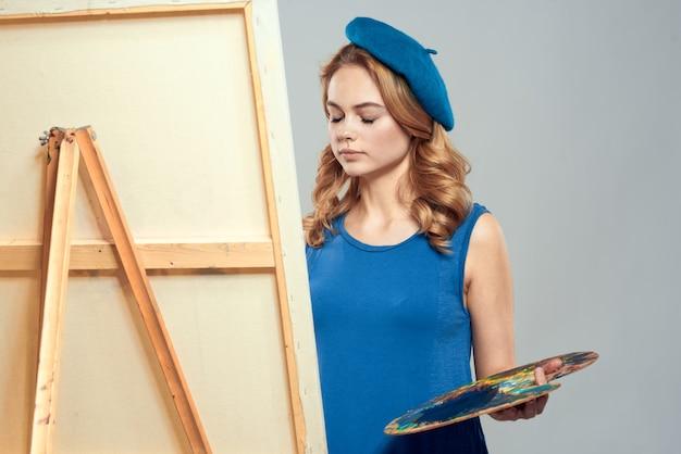 Artiste femme avec des peintures de béret bleu sur chevalet
