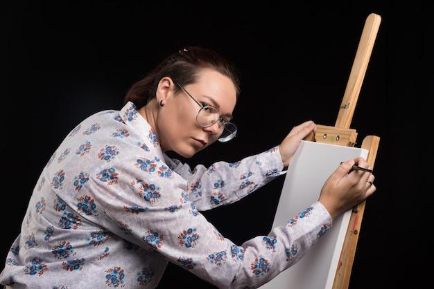 Artiste femme avec pinceau et peintures dans ses mains se tient près du chevalet et regarde la caméra. photo de haute qualité