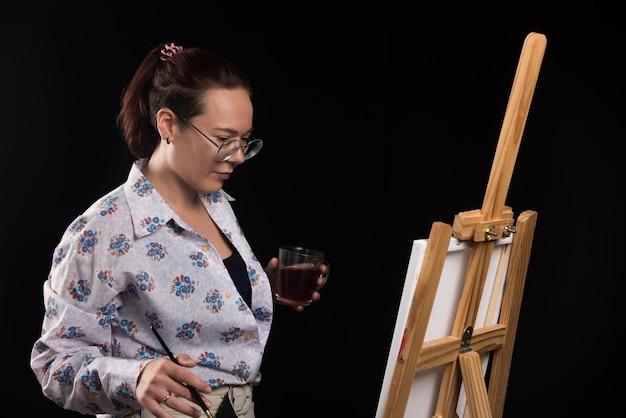 Artiste de femme tenant le pinceau et regardant la toile sur le noir