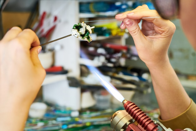 Artiste formant des perles de verre en flamme