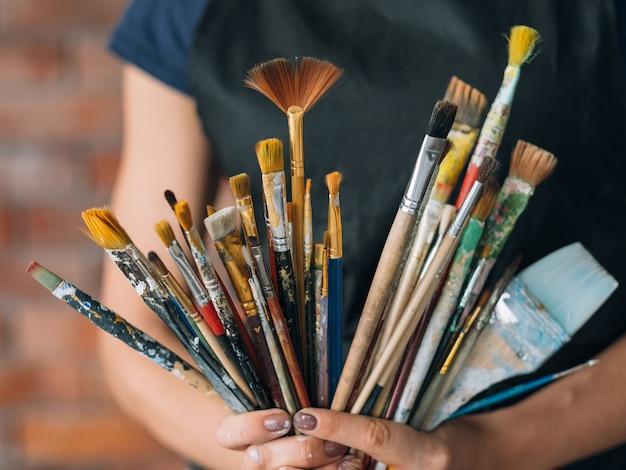 Artiste et fournitures d'art. des outils pour les talents. femme peintre en tablier posant avec un bouquet de pinceaux
