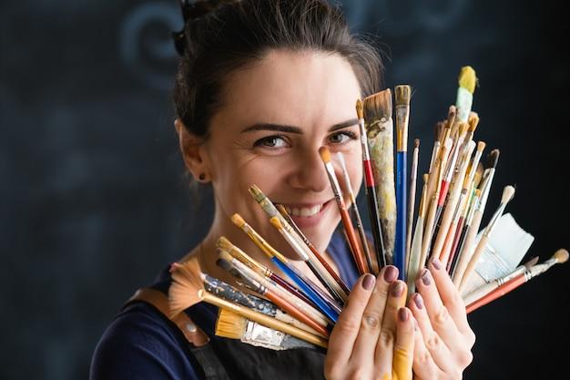 Artiste et fournitures d'art. souriante jeune femme avec assortiment de pinceaux. disposition de ventilateur d'outils.