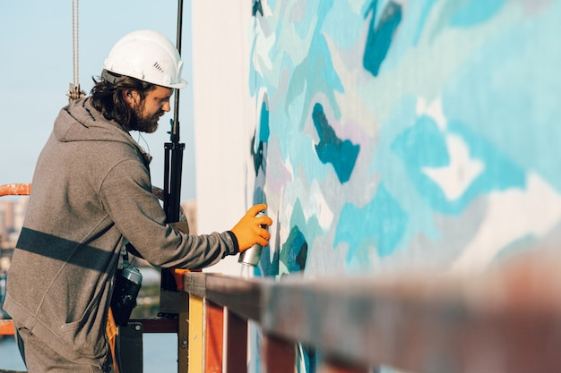 L'artiste graffeur peint un mur blanc à haute altitude dans les vagues.