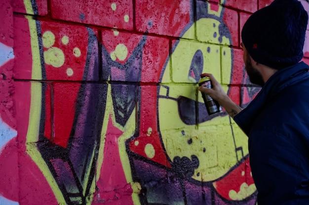 Artiste graffeur de rue avec de beaux dessins sur le mur de la ville