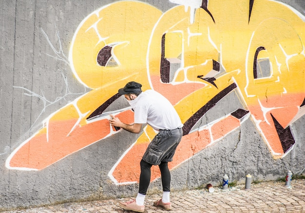 Artiste graffiti couvrant son visage tout en peignant avec un spray de couleur sur le mur. concept de street art urbain