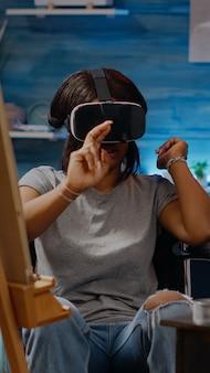 Artiste handicapé afro-américain avec technologie de lunettes vr pour le concept de dessin au studio. femme noire invalide en fauteuil roulant utilisant des lunettes de protection pour la création de chefs-d'œuvre modernes