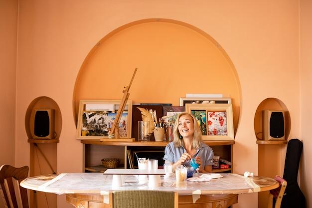 Une artiste heureuse chante une chanson dans son studio en mélangeant des peintures. des moments heureux de la vie. travail en atelier créatif. peintures d'intérieur. conception et inspiration. travail à la maison. mode de vie.