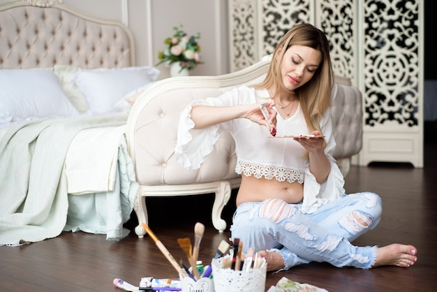 Artiste jeune femme enceinte peint photo sur toile avec des peintures à l'huile dans son atelier