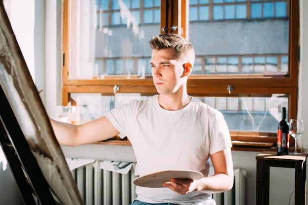 Artiste de jeune homme peint une image