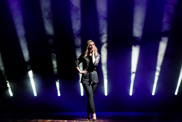 Artiste jolie femme sur l'arrière-plan de projecteurs flous sur la scène