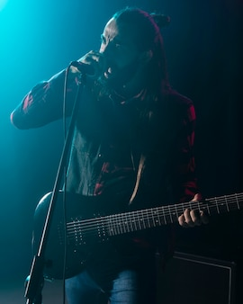 Artiste jouant de la guitare et chantant dans le microphone