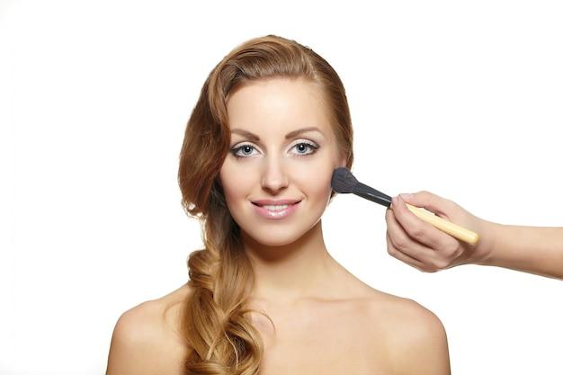 Artiste maquilleur appliquant le maquillage à une jolie femme blonde