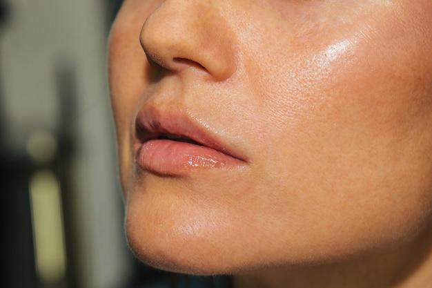 L'artiste maquilleur applique un éclat de rouge à lèvres rose. beau visage féminin. main d'un maquillage maître peignant les lèvres d'un modèle de beauté de jeune fille. maquillage en cours.