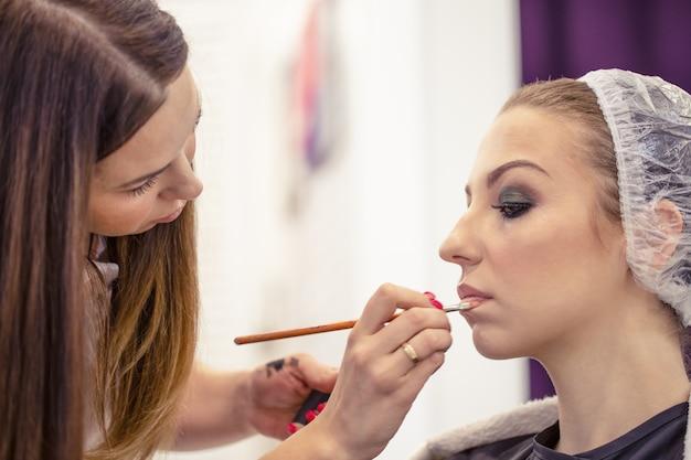 Artiste maquilleur applique le maquillage sur les lèvres d'une belle jeune fille avec une brosse