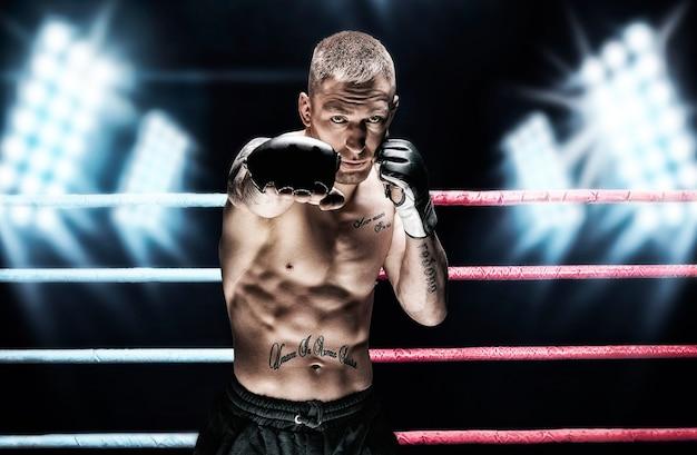 Artiste martial mixte posant dans le ring contre les projecteurs. concept de mma, ufc, boxe thaï, boxe classique. technique mixte