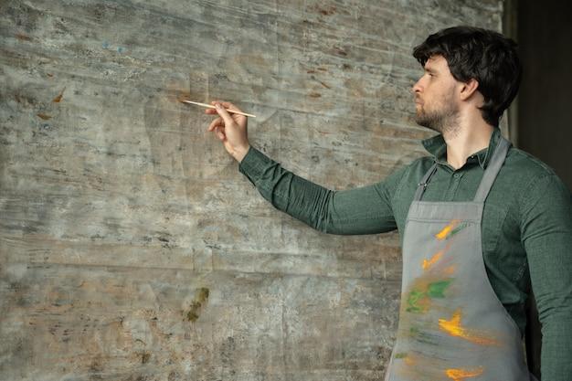 Artiste masculin concentré dessine sur chevalet dans sa vue de côté de studio d'art