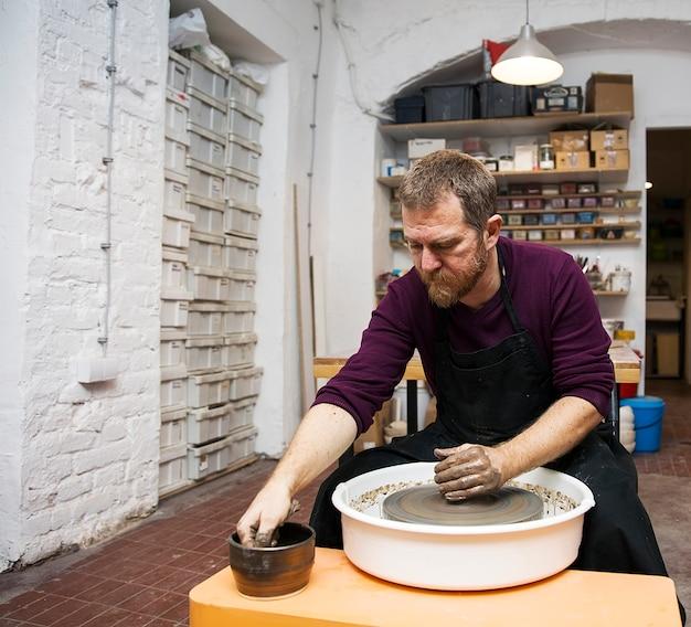 Artiste masculin fait la poterie d'argile sur une roue de rotation