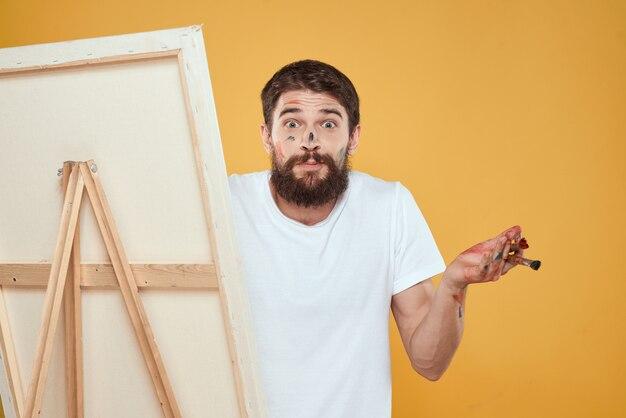 Artiste masculin peint une image sur toile avec un chevalet