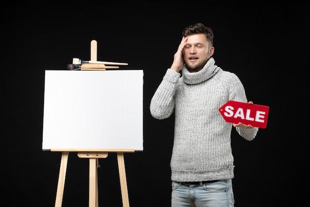 Artiste masculin réfléchi tenant l'inscription de vente sur le noir