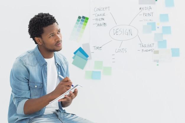 Artiste masculin réfléchie, écrivant des notes devant le tableau blanc au bureau