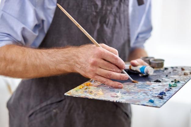 Artiste mélanger les couleurs sur la palette tenant en main se bouchent. créativité, concept artistique