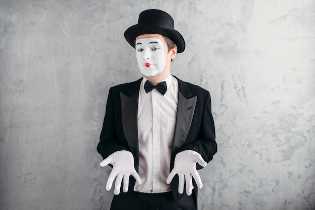 Artiste mime masculin drôle avec du maquillage dans des gants et un chapeau.