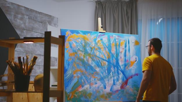 Artiste peignant au rouleau sur grande toile dans un atelier d'art.