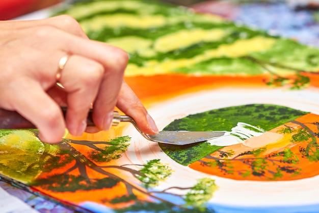 L'artiste peint un paysage à la gouache à l'aide d'un couteau à mastic
