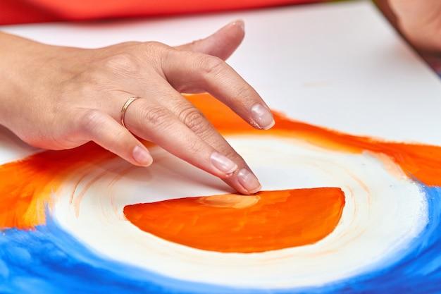 L'artiste peint un paysage à la gouache à l'aide des doigts