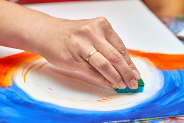L'artiste peint un paysage à la gouache à l'aide d'une éponge en mousse