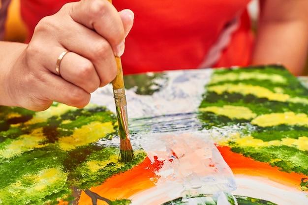 Artiste peint un paysage à la gouache à l'aide d'un pinceau
