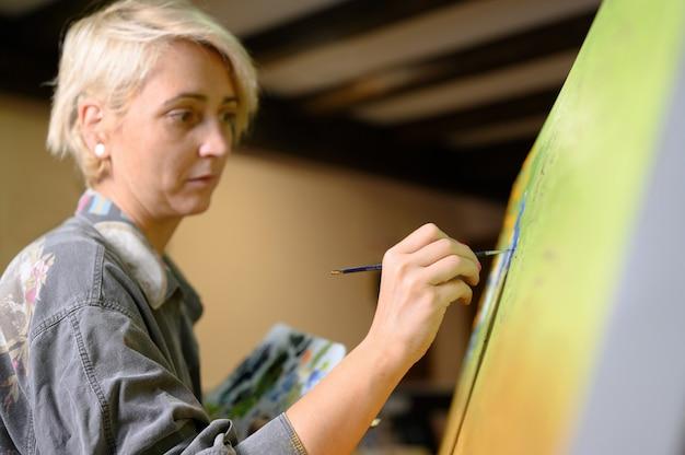 Artiste peintre femme peintre concentrée et inspirée, tableau avec pinceau et couleurs à l'huile sur toile