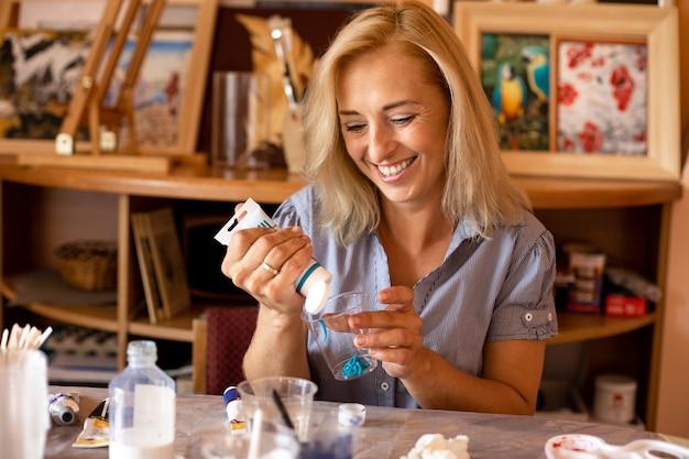 L'artiste qui rit commence à travailler avec un tube de peinture acrylique turquoise. travail en atelier créatif. peintures d'intérieur. conception et inspiration. travail à la maison. mode de vie.