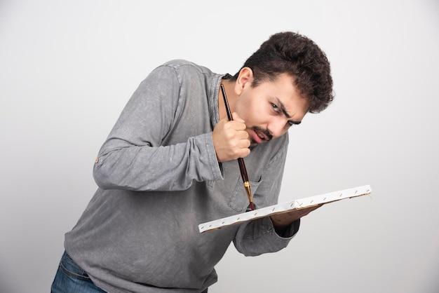 Artiste regardant son client très attentivement pour peindre le portrait détaillé.