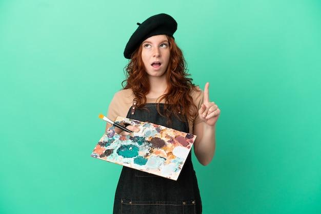 Artiste rousse adolescent tenant une palette isolée sur fond vert dans l'intention de réaliser la solution tout en levant un doigt vers le haut