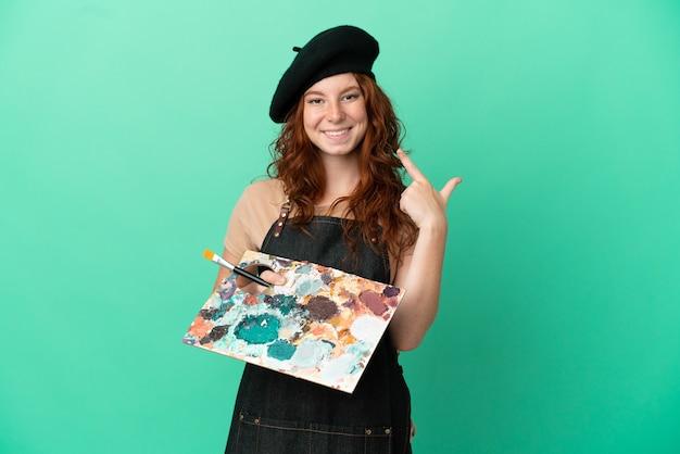 Artiste rousse adolescent tenant une palette isolée sur fond vert donnant un geste de pouce levé