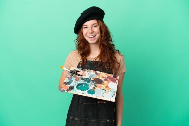 Artiste rousse adolescent tenant une palette isolée sur fond vert avec une expression faciale surprise