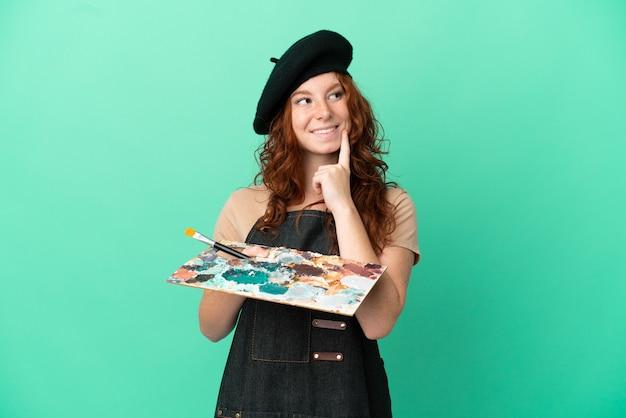 Artiste rousse adolescent tenant une palette isolée sur fond vert pensant une idée tout en levant