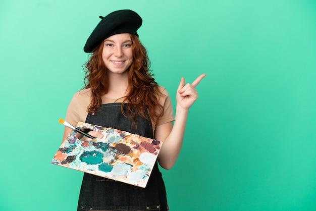 Artiste rousse adolescent tenant une palette isolée sur fond vert, pointant le doigt sur le côté