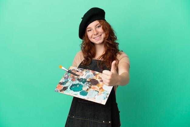 Artiste rousse adolescent tenant une palette isolée sur fond vert avec les pouces vers le haut parce que quelque chose de bien s'est produit