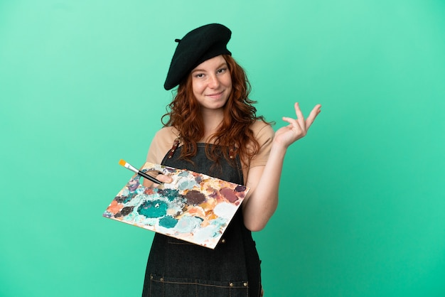 Artiste rousse adolescent tenant une palette isolée sur fond vert tendant les mains sur le côté pour inviter à venir