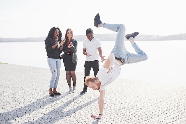 Artiste de rue breakdance en plein air. des amis surpris applaudissent