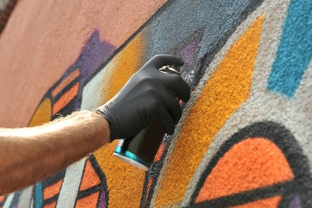 L'artiste de rue dessine des graffitis colorés sur le mur de béton concept d'art moderne coloré