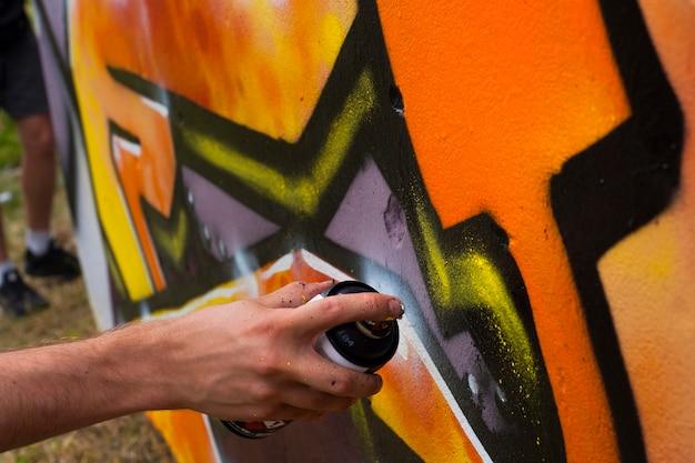 Artiste de rue dessine des graffitis colorés sur le mur de béton.