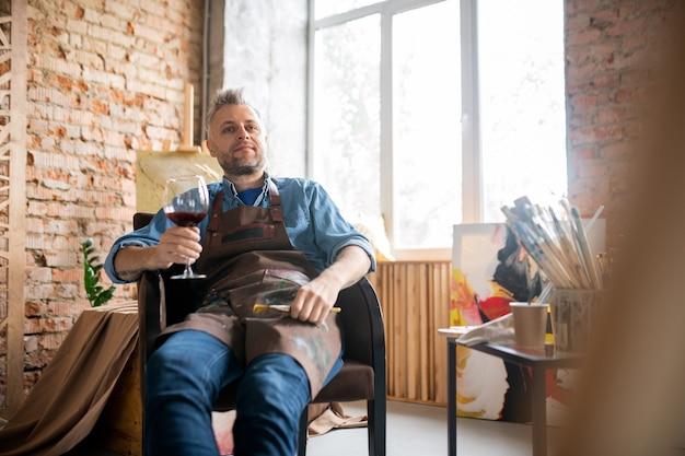 Artiste satisfait en vêtements de travail ayant un verre de vin rouge tout en profitant d'une pause après le travail sur une nouvelle peinture en studio